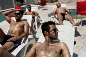 A group of young men takes sun bath in a private complex in Royan (Northern Iran). Although Islamic morals are taken laxly in private areas in Northern Iran, gender segregation in the swimming pool is still strictly controlled. Photo: Kaveh Rostamkhani