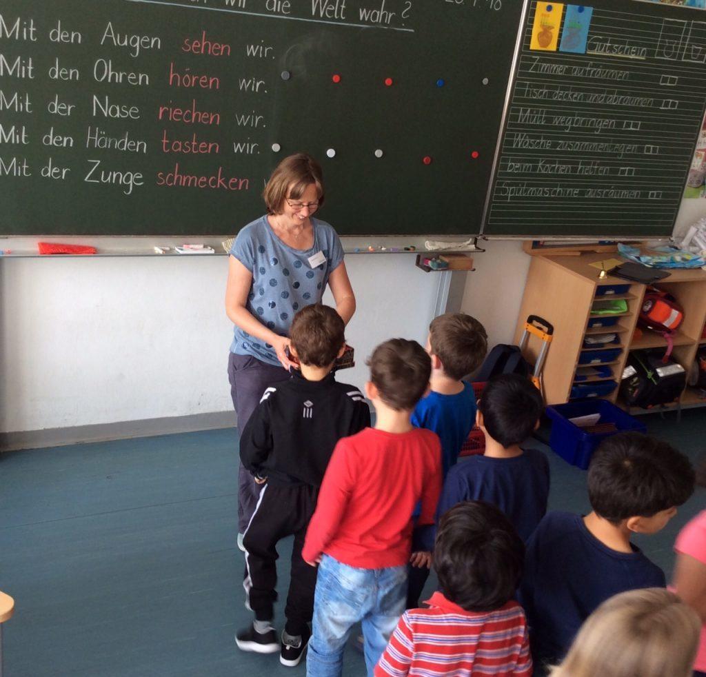 Kinder in einer Schlange vor der Bibliothekarin: Die Gefühlkärtchen werden gezogen.