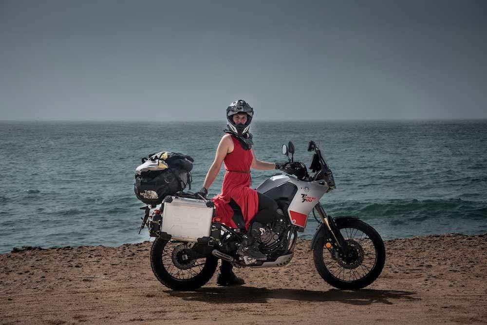 Lea Rieck mit dme Motorrad in der Western Sahara vor dem Meer.