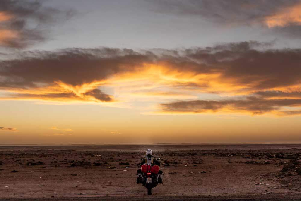 Mit dem Motorrad in den Sonnenaufgang fahren, Western Sahara. Foto: Lea Reck