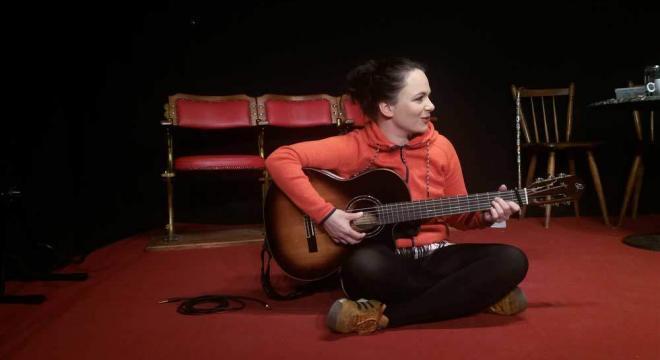 Katrin Freiburghaus auf dem Boden sitzend, dabei eine Gitarre spielen. Foto von Fee Brembeck.